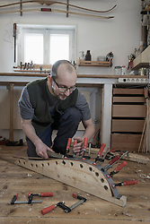 Male bow maker fixing wood in bow shape in workshop, Bavaria, Germany