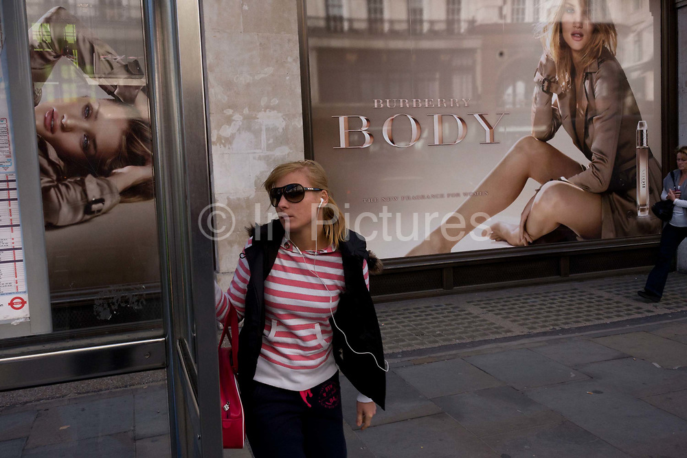 A young woman awaits a bus in front of a large ad billboard for the Body fragrance Burberry Group plc. a British luxury fashion house, manufacturing clothing, fragrance, and fashion accessories. Rosie Alice Huntington-Whiteley (born 18 April 1987) is an English model and actress unveiled as the face of Burberry's newest fragrance, Burberry Body, in July 2011 but also best known for her work for Victoria's Secret, Burberry, and her role as Carly Spencer in the 2011 film Transformers: Dark of the Moon, part of the Transformers film series