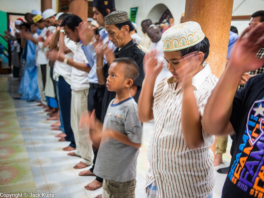 """08 AUGUST 2013 - BANGKOK, THAILAND: Men pray during Eid al-Fitr services at Haroon Mosque in Bangkok. Eid al-Fitr is the """"festival of breaking of the fast,"""" it's also called the Lesser Eid. It's an important religious holiday celebrated by Muslims worldwide that marks the end of Ramadan, the Islamic holy month of fasting. The religious Eid is a single day and Muslims are not permitted to fast that day. The holiday celebrates the conclusion of the 29 or 30 days of dawn-to-sunset fasting during the entire month of Ramadan. This is a day when Muslims around the world show a common goal of unity. The date for the start of any lunar Hijri month varies based on the observation of new moon by local religious authorities, so the exact day of celebration varies by locality.      PHOTO BY JACK KURTZ"""