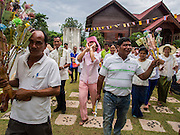 29 JUNE 2014 - DAN SAI, LOEI, THAILAND: People dance through the grounds of Wat Ponchai during a merit making procession on the last day of the Ghost Festival in Dan Sai. Phi Ta Khon (also spelled Pee Ta Khon) is the Ghost Festival. Over three days, the town's residents invite protection from Phra U-pakut, the spirit that lives in the Mun River, which runs through Dan Sai. People in the town and surrounding villages wear costumes made of patchwork and ornate masks and are thought be ghosts who were awoken from the dead when Vessantra Jataka (one of the Buddhas) came out of the forest. On the last day of the festival people participate in merit making ceremonies at the Wat Ponchai in Dan Sai and lead processions through town soliciting donations for the temple.    PHOTO BY JACK KURTZ