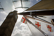 High winds and wet weather herald an uncertain week in the Britain less than 24 hours before the UK's general election. English flags on a tourist kiosk hang below the Elizabeth Tower containing the bell known as Big Ben. Recent showers has made the capital wet and so tourist trinkets and souvenirs have been covered with clear sheeting. We see the monarch the Queen, peering through the rain-soaked sheeting with the tall height of Elizabeth Tower. English flags hang limp after the soaking but sunlight is coming from behind the clock tower, the Gothic architecture of Victoria architect Pugin's building, the seat of parliamentary government in the UK.