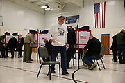 """11082016 - Bloomington, Indiana, USA: A voter wearing a t-shirt with a photo of Bill and Hillary Clinton, and the words, """"Do Not Resuscitate,"""" casts his ballot at St. John's Catholic Church on Election Day 2016. The church had a line of over 100 voters in line by 5:45 a.m., and the polls opened at 6 a.m. Election officials are expecting a record turnout that will surpass 2008 record. The presidential race between Hillary Clinton and Donald Trump has left the United States divided. (Jeremy Hogan/Polaris)"""