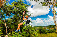A woman ziplining in the jungle with Alltournative Mayan Offtrack Adventures, near Riviera Maya, Mexico.