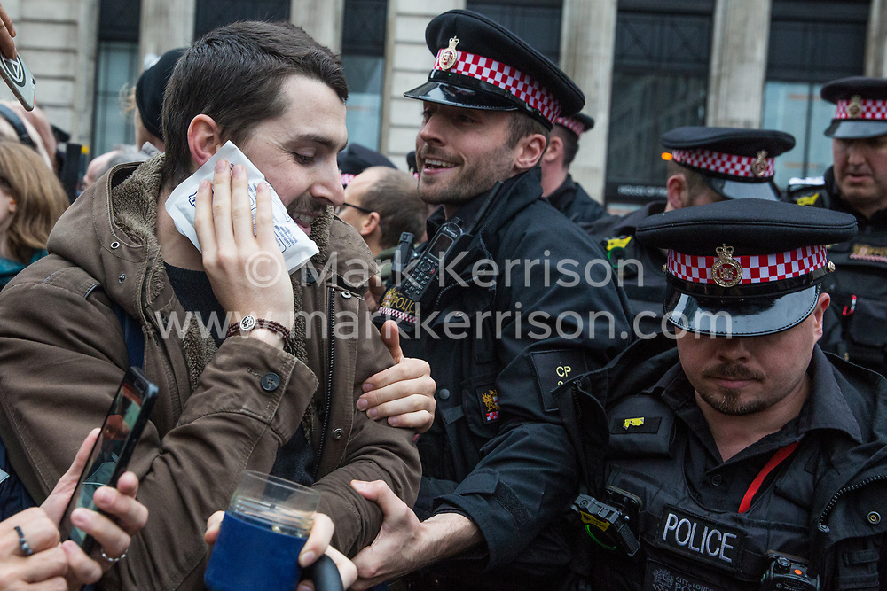 London, UK. 14 October, 2019. Police officers push back a climate activist from Scientists for Extinction Rebellion who been assaulted by a member of the public when blocking the busy junction at King William Street in front of London Bridge on the eighth day of International Rebellion protests across London. Today's activities were concentrated around the  City of London's finance district.