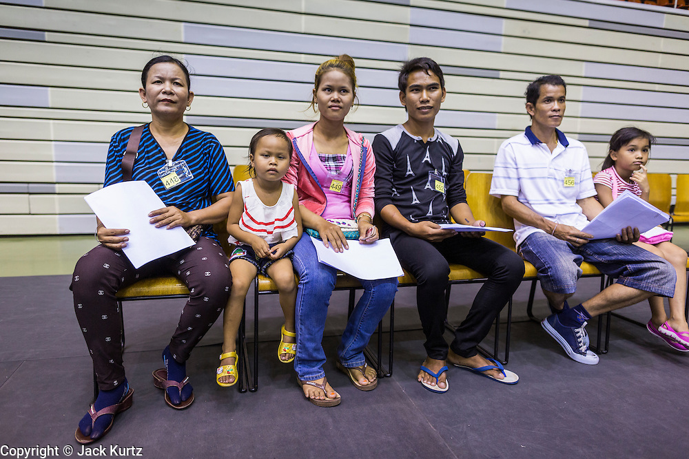 """17 JULY 2014 - BANGKOK, THAILAND: Undocumented Cambodian migrant workers wait to be called for ID cards at the temporary """"one stop service center"""" in the Bangkok Youth Center in central Bangkok. Thai immigration officials have opened several temporary """"one stop service centers"""" in Bangkok to register undocumented immigrants and issue them temporary ID cards and work permits. The temporary centers will be open until August 14.    PHOTO BY JACK KURTZ"""