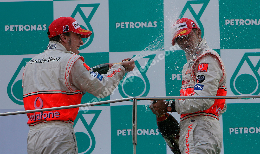 McLaren-Mercedes drivers Fernando Alonso and Lewis Hamilton celebrate with champagne on the podium after the 2007 Malaysian Grand Prix in Sepang. Photo: Grand Prix Photo