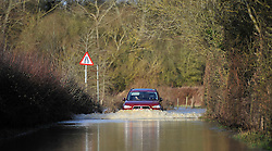 © Licensed to London News Pictures. 27 January 2013. Ascott Under Wychwood, Oxfordshire. Car drives through flooded road. Floods after the snow melted. Photo credit : MarkHemsworth/LNP