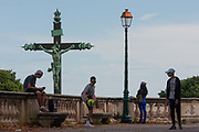 Local French teenagers mess about with a ball in Place Royal du Peyrou where the presence of a large crucified Christ looks down on their youth and boredom, on 18th June 2016, in Montpellier, France.