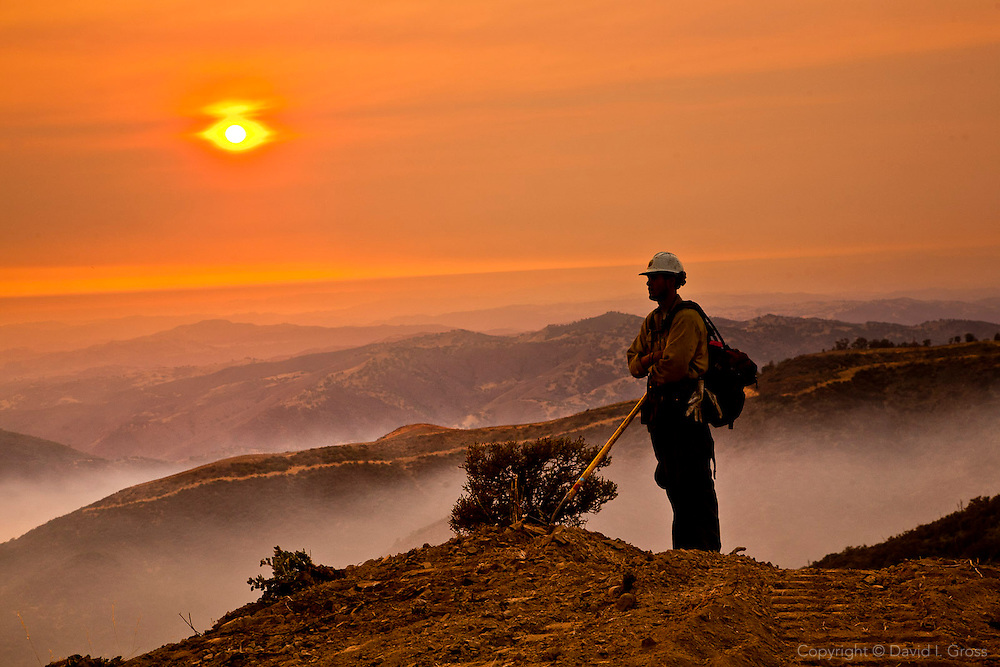 Joseph Darling of the Kern Valley Hotshots watches the fire line at the end of the day during the La Brea Fire in California.