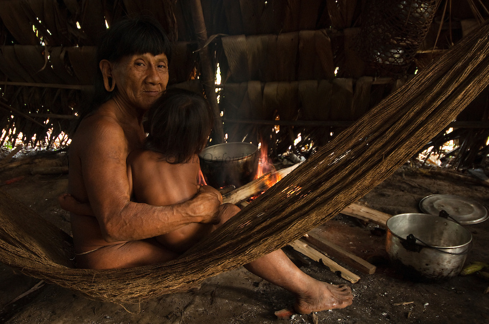 Huaorani Indian woman, Bebanca Wane and child in hammock inside their hut.<br /> Bameno Community. Yasuni National Park.<br /> Amazon rainforest, ECUADOR.  South America<br /> This Indian tribe were basically uncontacted until 1956 when missionaries from the Summer Institute of Linguistics made contact with them. However there are still some groups from the tribe that remain uncontacted.  They are known as the Tagaeri & Taromenane. Traditionally these Indians were very hostile and killed many people who tried to enter into their territory. Their territory is in the Yasuni National Park which is now also being exploited for oil.