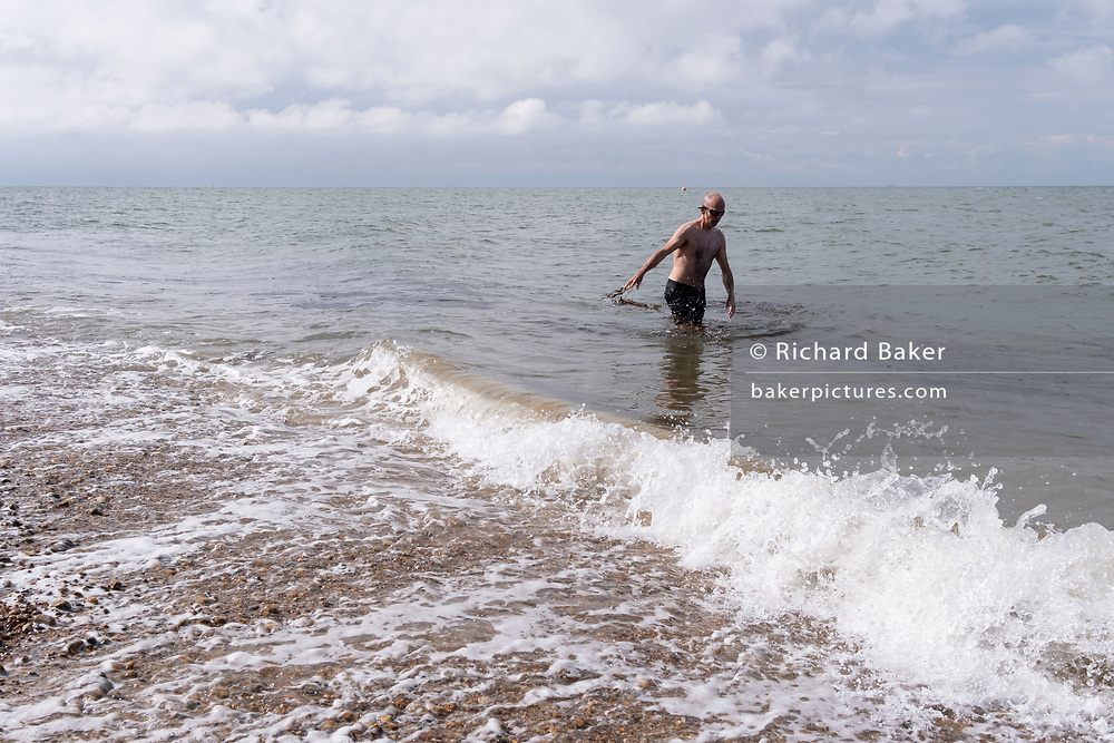 A sea swimmer walks out of the tidal waters of the Thames Estuary, on 25th July 2021, in Whitstable, England.