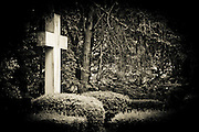 A dark image of a cross in a cemetery in Rochester, NY. Missoula Photographer