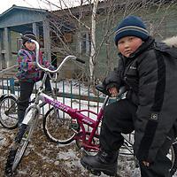 Russian school children in arctic village of Nizhnyaya Pesha pose on bikes outside family home.