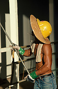 Chinese construction worker with sun hat and hard hat combination, Hong Kong, China