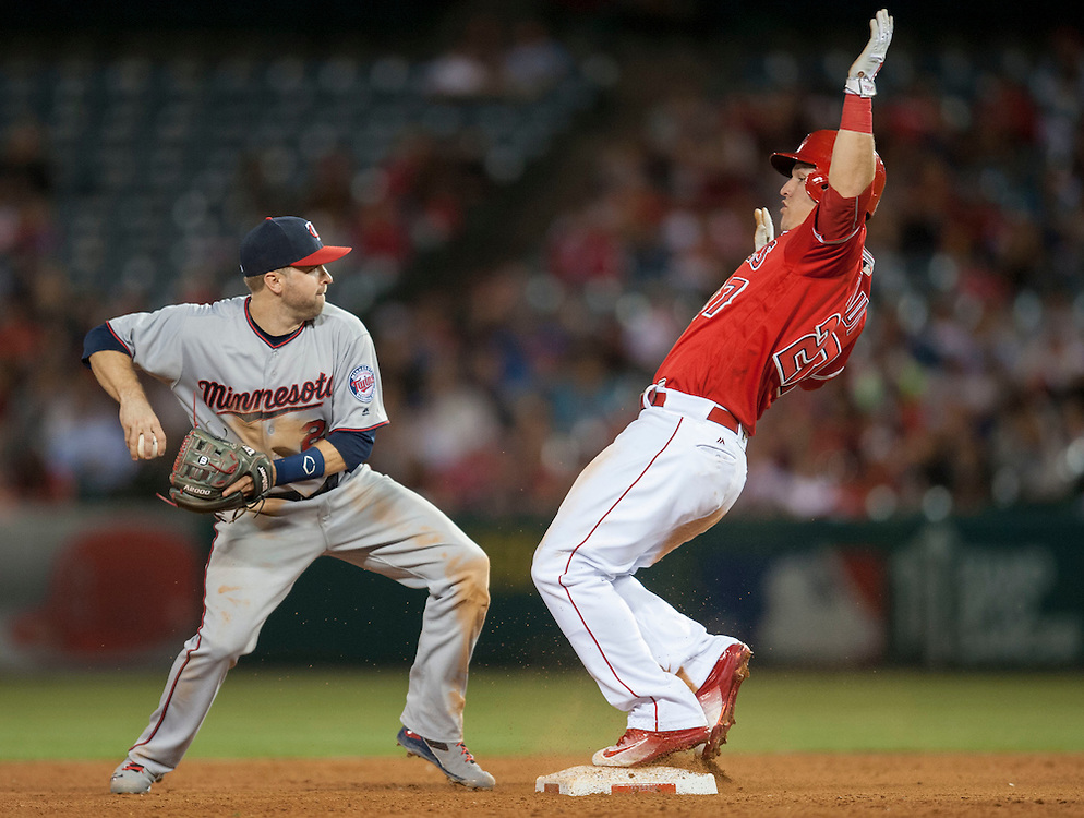 The Angels' Mike Trout pops up after sliding safely into second as the Twins' Brian Dozier looks to throw to first in the fifth inning Wednesday night at Angel Stadium.<br /> <br /> ///ADDITIONAL INFO:   <br /> <br /> angels.0616.kjs  ---  Photo by KEVIN SULLIVAN / Orange County Register  -- 6/15/16<br /> <br /> The Los Angeles Angels take on the Minnesota Twins Wednesday at Angel Stadium.