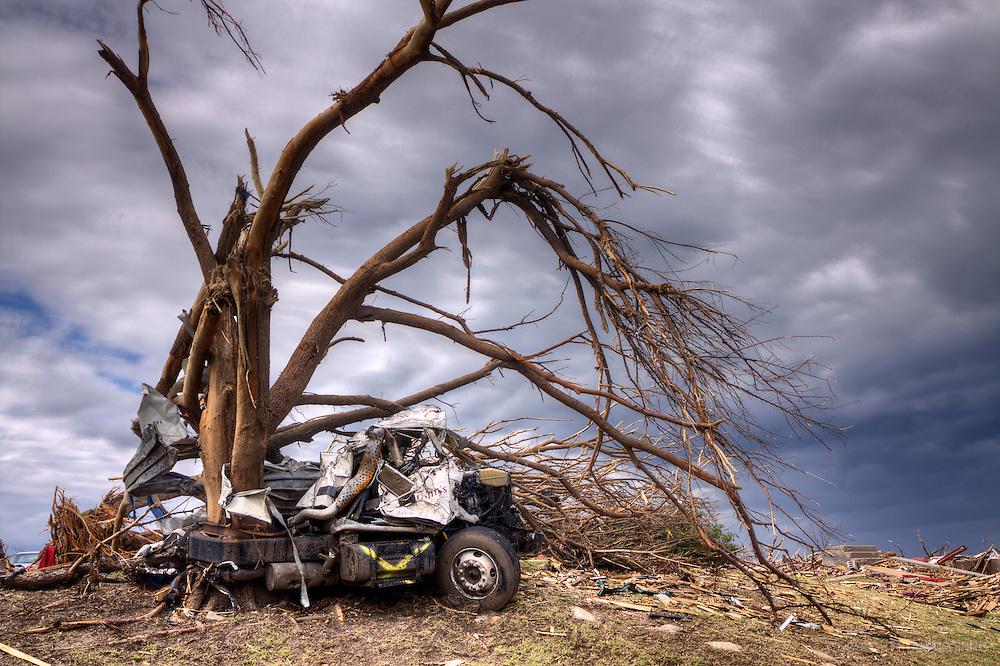 A Saint John's semi truck is wrapped around a debarked tree in Joplin, Missouri, May 25, 2011.   On May 22, 2011, Joplin Missouri was devastated by an EF-5 tornado.