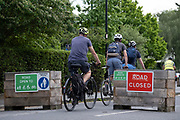 Cyclists pass through the barriers that form an LTN (Low Traffic Neighbourhood), an experimental closure by Southwark Council preventing motorists from accessing the junction of Carlton Avenue and Dulwich Village. Restrictions also prevent traffic from passing through at morning and afternoon rush-hour times in the borough of Southwark, on 14th June 2021, in London, England.