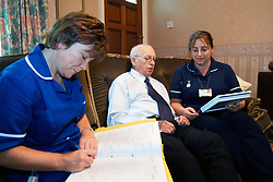 Discharged elderly patient is visited in his home by two district nurses Bradford Yorkshire UK