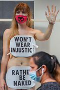 A pedestrian wearing a face mask pass by the windows of the H&M as an Extinction Rebellion activist glued themselves to the shop window of H&M in Oxford street in London looks at the members of the public passing by and greeting them on Wednesday, Sept 9, 2020. The activists are completely naked, except for strategically placed placards that made a statement about social and environmental injustice in the fashion industry. The signs read 'Fashion is F*cked, Rather Be Naked', 'Won't Wear Injustice, Rather be Naked' and 'Not Buying This Bullshit, Rather Be Naked'. Environmental nonviolent activists group Extinction Rebellion enters its 9th day of continuous ten days protests to disrupt political institutions throughout peaceful actions swarming central London into a standoff, demanding that central government obeys and delivers Climate Emergency bill. (VXP Photo/ Vudi Xhymshiti)