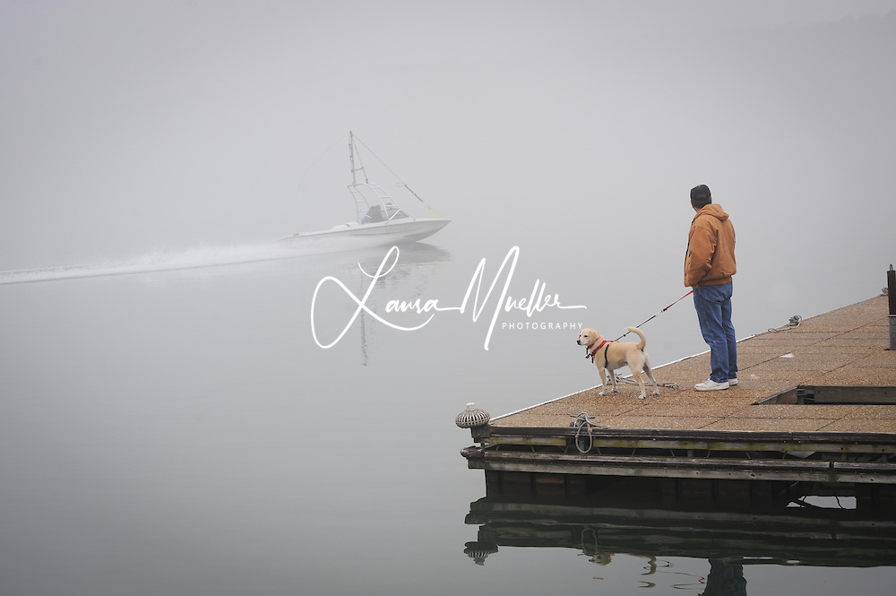 Sherrills Ford, NC - Charlie Glassey of Terrell and his dog Hotrod watch from the Lake Norman Marina dock as the towboat makes a test run in the morning fog prior to the 33rd Annual Lake Norman New Years Day Barefoot Challenge. <br /> photo © Laura Mueller - www.lauramuellerphotography.com