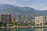 The coastal buildings and mountains that surround the inlet for the harbor of Carabellada, Venezuela.