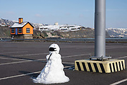 A snow person sit's alone in the car park at the Folkestone Harbour Arm, shortly after the sun came out and most of the snow on the ground melted, just a few snow people remained on the 11th of February 2021, Folkestone, United Kingdom. In the background sits an orange bungalow on the edge of Folkestone harbour built by the artist Richard Woods as part of the 2017 Folkestone Triennial. The artist wanted to create a piece about the housing crisis in the UK.