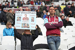 A young West Ham United fan holds up a tribute to Mark Noble ahead of the Premier League match at the London Stadium
