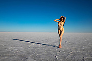 Photo of a woman posing at sunset on the Bonneville Salt Flats, Utah with tire marks extending into the distance.