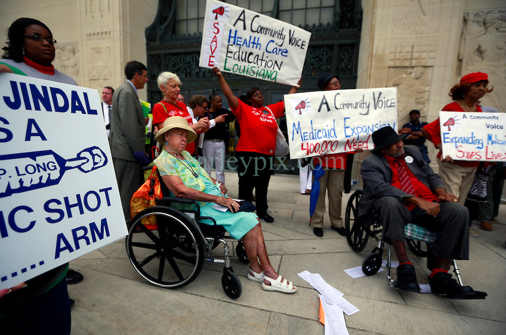 30 April 2013. Baton Rouge, Louisiana,  USA. .March on Baton Rouge, Enough is Enough. Wheel chair bound Lanny Roy and Patricia Eberhardt attend a  coalition of 40 Louisiana Organisations protesting what many believe to be the 'Economic and fiscal disaster that is the administration of Governor Bobby Jindal.' Top of the agenda,  Jindal's refusal to accept the expansion of MEDICAID, instead denying coverage to over 400,000 citizens with Jindal refusing to accept federal funding for  'Obamacare.' Slashed state spending on education, social services and critical community based organisations is having far reaching and devastating effects on ordinary and poor citizens in Louisiana..Photo; Charlie Varley.