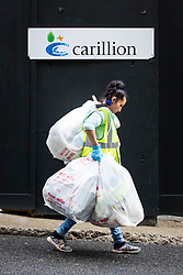 © Licensed to London News Pictures. 15/01/2018. London, UK. Rubbish bags are carried away from a closed Carillion construction site in central London. The construction firm has gone into liquidation after losing money on big contracts and running up debts of around £1.5bn. Photo credit: Rob Pinney/LNP