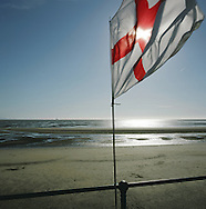 A cross of St. George England flag fluttering in the wind on the beach at Crosby, Merseyside at the mouth of the river Mersey. The Mersey is a river in north west England which stretches for 70 miles (112 km) from Stockport, Greater Manchester, ending at Liverpool Bay, Merseyside. For centuries, it formed part of the ancient county divide between Lancashire and Cheshire.