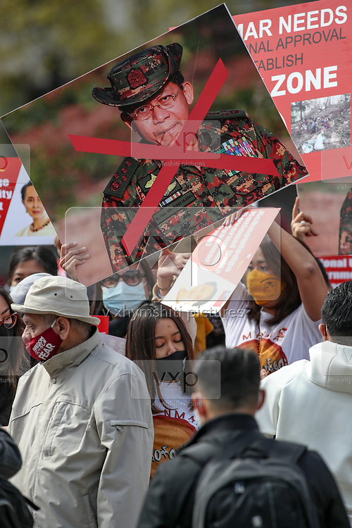 A protestor holds a banner with a portrait of Min Aung Hlaing who is the head of Myanmar's military regime during a protest against Myanmar's ruling junta as they gather and chant outside the Houses of Parliament, Westminster Palace in London on Sunday, May 2, 2021. This is a series of protests following the locked out of the Myanmar envoy to the UK from the embassy three weeks ago on April 7. Myanmar's ambassador to the UK, Kyaw Zwar Minn, said the embassy has been seized by the military attache. (Photo/ Vudi Xhymshiti)