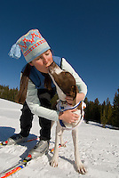 A young woman kisses her dog after skiing in Wyoming.