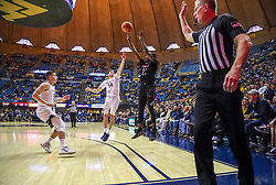 Dec 14, 2019; Morgantown, WV, USA; Nicholls State Colonels guard Dexter McClanahan (22) shoots a three pointer while guarded by West Virginia Mountaineers guard Chase Harler (14) and West Virginia Mountaineers guard Jordan McCabe (5) during the first half at WVU Coliseum. Mandatory Credit: Ben Queen-USA TODAY Sports