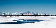 Winter at the Henrys Fork River at Island Park Idaho, crowned by the Grand Teton Mountains beyond.