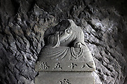 a decapitated Buddhist sculpture in a Yagura Japan