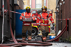"""© Licensed to London News Pictures. 16/11/2019. Bolton, UK. Firefighters rescue a resident's pet hamster as they work at the scene where a fire broke out overnight (15th/16th November 2019) at a block of flats known as """" The Cube """" , in Bolton Town Centre . At least two people are known to have been treated by paramedics at the scene of the six-story , block which is occupied by students of the University of Bolton . Photo credit: Joel Goodman/LNP"""