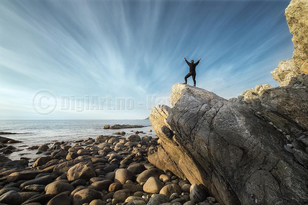 Women on top of a clip salutes the ocean, with a dramatic sky in the background  Dame på toppen av en klippe hilser til havet, med en dramatisk himmel i bakgrunnen.