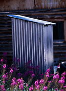 Hearing protection required during hail storms!  Aluminum outhouse snugged close to log home in Carcross, Yukon Territory, Canada.