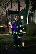 A firefighter on duty on a stormy night.