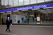 Businessman in suit and coat walks past the new entrance to Farringdon Station in London, UK.