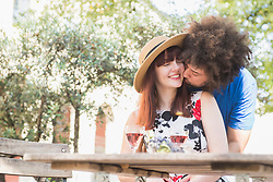 Young couple kissing at outdoor restaurant