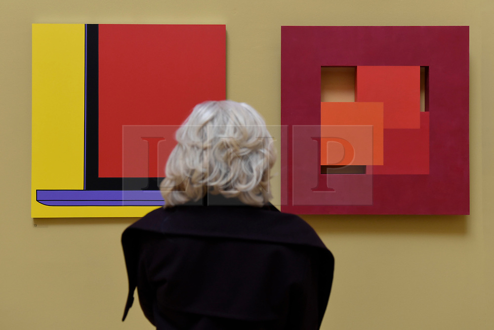"""© Licensed to London News Pictures. 08/06/2017. London, UK. A visitor views (L to R) """"Untitled (Yellow Laptop Fragment)"""" by Sir Michael-Craig Martin RA (GBP40,000) and """"Thirds"""" by John Carter RA (GBP10,000). Preview of the Summer Exhibition 2017 at the Royal Academy of Arts in Piccadilly.  Co-ordinated by Royal Academician Eileen Cooper, the 249th Summer Exhibition is the world's largest open submission exhibition with around 1,100 works on display by high profile and up and coming artists.<br />  Photo credit : Stephen Chung/LNP"""