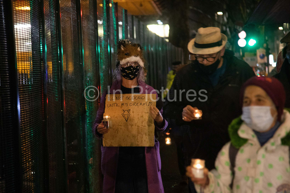 Environmental anti-HS2 activists attend a candlelit vigil at Euston Gardens on the 6th of February 2021, London, United Kingdom. A woman bears the the words by Iggy Fox in commemoration of his untimely death. Anti HS2 campaigners and climate activists have occupied the garden and the trees outside Euston train station for months. The vigil is for the trees which have already been cut down and to commemorate the climate activist Iggy Fox Raphaël Coleman who died a year ago. Because of Covid-19 restrictions all were asked to constantly move and not stay too close. A number of tree protectors have been under ground for 11 days in tunnels dug out over months and bailiffs and the National Eviction Team are working day and night to dig them out. The high speed train project, HS2, will run from London to Birmingham, Manchester and Leeds and it is estimated to cost around 100bn pounds. The garden and trees have to go because HS2 wants to build a temporary taxi rank as part of the bigger high speed train project.