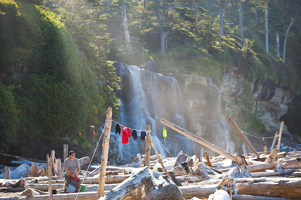 A man packs up camp on the beach at Tsusiat Falls, West Coast Trail, British Columbia, Canada.