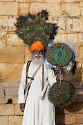 Street vendor selling peacock feather fans at Jaisalmer Fort, the 'Golden Fort'. It is one of the largest forts in the world. Jaisalmer, Rajasthan, India