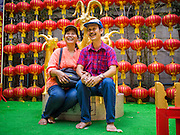 """19 FEBRUARY 2015 - BANGKOK, THAILAND: A couple is photographed next to a statue of a goat on Chinese New Year at Wat Mangkon Kamalawat in Bangkok. 2015 is the Year of Goat in the Chinese zodiac. The Goat is the eighth sign in Chinese astrology and """"8"""" is considered to be a lucky number. It symbolizes wisdom, fortune and prosperity. Ethnic Chinese make up nearly 15% of the Thai population. Chinese New Year (also called Tet or Lunar New Year) is widely celebrated in Thailand, especially in urban areas that have large Chinese populations.    PHOTO BY JACK KURTZ"""