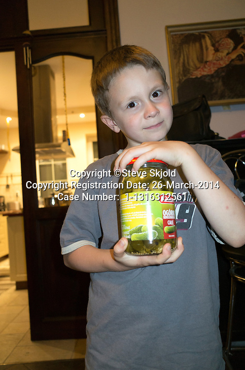 Polish boy age 10 holding a large jar of pickles, his favorite food. Zawady Central Poland