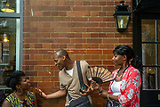 A man and two women converse on the street at the African street style Festival, Hackney, London, United Kingdom.