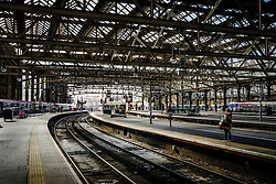 A woman passenger waits on a platform at Glasgow Central Station - the major mainline rail terminus in Glasgow, Scotland<br /> <br /> (c) Andrew Wilson | Edinburgh Elite media